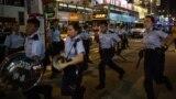 Rendőrök érkeznek feloszlatni egy kezdődő tüntetést Hongkongban, 2014. november 26-án