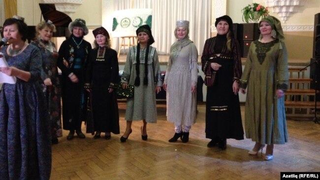 Илмира Васил (с) үзе теккән татар күлмәкләрен күрсәтә