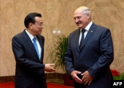 Chinese Prime Minister Li Keqiang (left) speaks with visiting Belarusian President Alyaksandr Lukashenka in Beijing on July 17.
