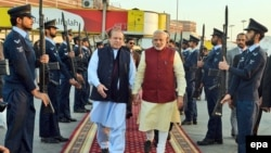 Indian Prime Minister Narendra Modi (C-R) being welcomed by the Prime Minister of Pakistan, Nawaz Sharif (C-L), at the airport in Lahore on December 25.