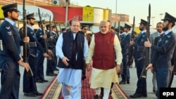 Indian Prime Minister Narendra Modi (center right) is welcomed by his Pakistani counterpart Nawaz Sharif at Lahore airport on December 25.