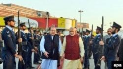 Indian Prime Minister Narendra Modi (C-R) being welcomed by the Prime Minister of Pakistan, Nawaz Sharif (C-L), at the airport in Lahore, Pakistan on December 25.