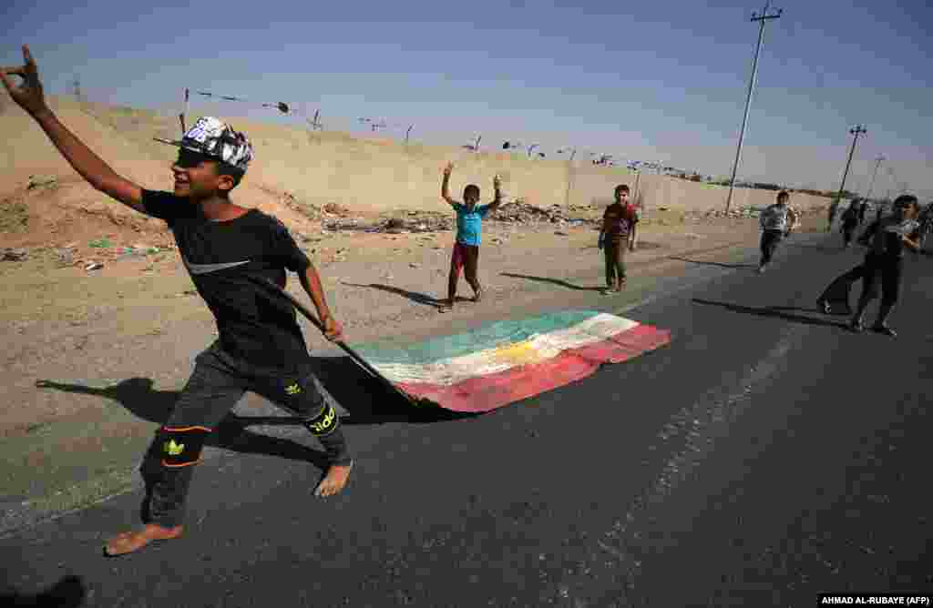 An Iraqi boy drags a Kurdish flag as Iraqi forces advance towards the center of Kirkuk during an operation against Kurdish fighters on October 16. (AFP/Ahmad al-Rubaye)