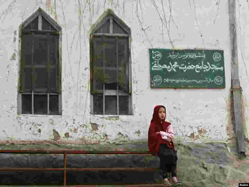 A girl sits in front of a mosque in Kabul. (REUTERS/Mohammad Ismail)