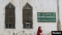 Një vajzë afgane ulur para një xhamie në Kabul, 2011