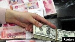 100 долларлық АҚШ валютасы және 100 юаньдық Қытай ақшасы. (Көрнекі сурет)