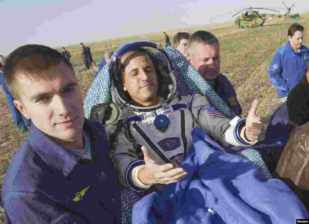 "Acaba soaks up the sun shortly after he is removed from the Soyuz capsule. ""It's good to be home,"" he said."