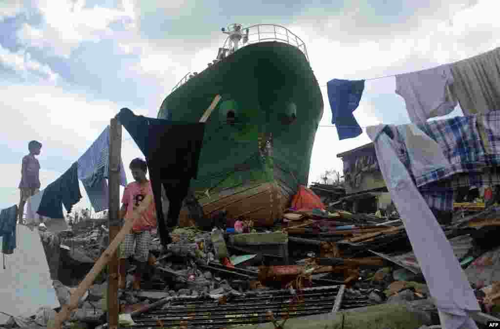 Мужчина бродит среди груды мусора и обломков кораблей после тайфуна