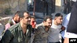 Сириски бунтовници апсат полицајци откако зазедоа полициска станица во Алепо на 25 јули 2012 година.