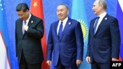 Президент Китая Си Цзиньпин (слева), президент Казахстана Нурсултан Назарбаев (в центре) и президент России Владимир Путин фотографируются после саммита ШОС. Астана, 9 июня 2017 года.