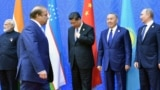 Pakistani Prime Minister Nawaz Sharif (second from left) walks past (left to right) Indian Prime Minister Narendra Modi, Chinese President Xi Jinping, Kazakh President Nursultan Nazarbaev, and Russian President Vladimir Putin as he arrives for group photo at the Shanghai Cooperation Council summit in Astana on June 9.