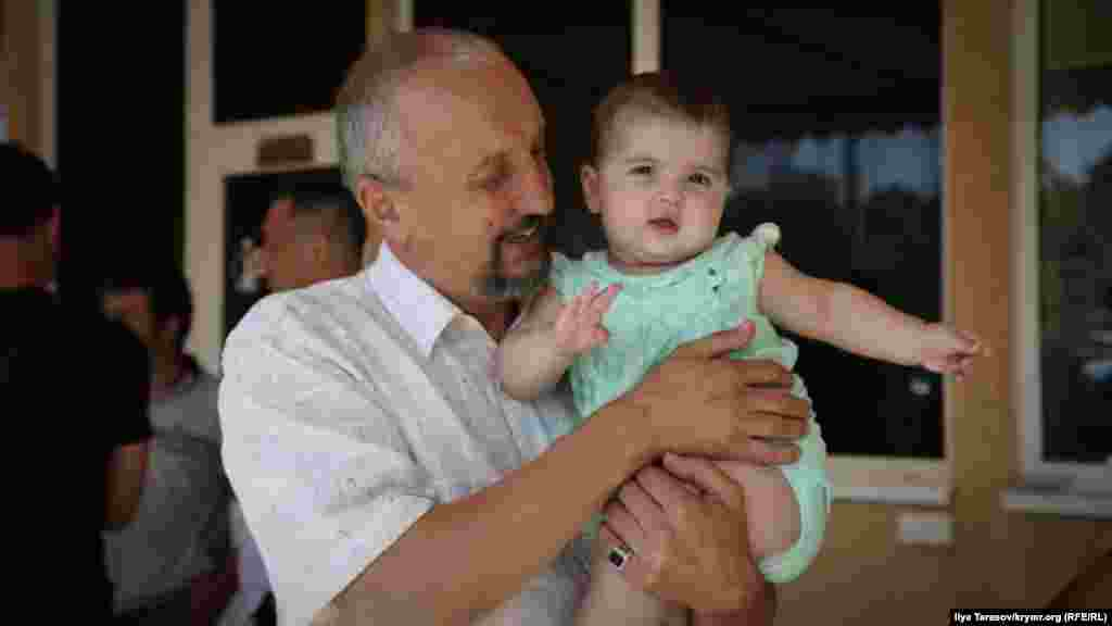 Рустем, отец Сервера Мустафаева, держит на руках Наджие, младшую дочь своего сына