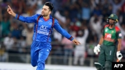 FILE: Rashid Khan (L) celebrates after taking a wicket in a Twenty20 cricket match.
