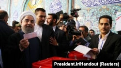 Iran's interior minister said President Hassan Rohani -- seen casting his ballot on May 19 -- won reelection with around 57 percent of the vote, easily avoiding a runoff.