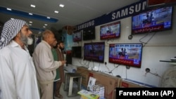FILE: Pakistani viewers watch news bulletins on television in Karachi.