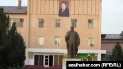 Türkmenistanyň öňki prezidenti S.Nyýazowyň monumenti we onuň araksyndaky binada häzirki prezident G.Berdimuhamedowyň portreti.