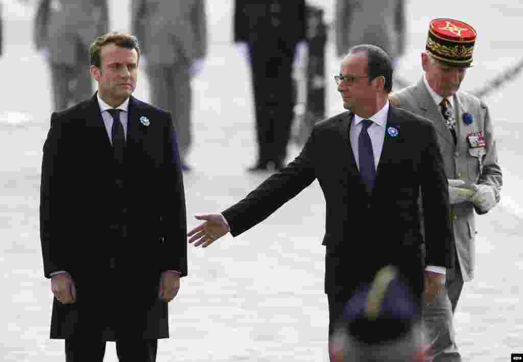 Current French President Francois Hollande (right) reaches out to touch President-elect Emmanuel Macron during a ceremony to mark Victory Day in Paris on May 8, the day after the latter convincingly beat his main rival, the far-right nationalist Marine Le Pen, in a presidential runoff. (epa/Francois Mori)