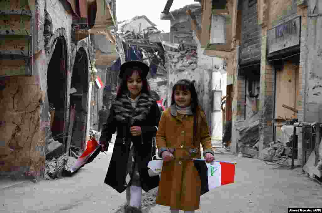 Iraqi girls walk holding their national flag toward a ceremony for the reopening of the Bab al-Saray market in the Old City of Mosul. (AFP/Ahmad Muwafaq)