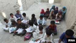 Pupils in the Kuchu village in southeastern province of Sistan and Baluchistan study in a ruined building.