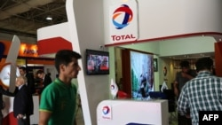 Iran -- People walk past the stand of French oil and gas company Total during Iran's annual International Oil, Gas, Refining & Petrochemical Exhibition in Tehran, May 06, 2015