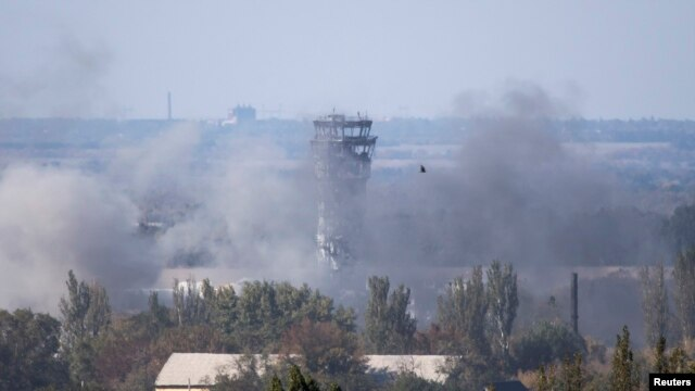 The traffic-control tower of Donetsk's Sergei Prokofiyev International Airport is seen through smoke during fighting between pro-Russian rebels and Ukrainian government forces in Donetsk on October 3.