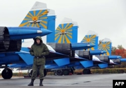 A Russian officer patrols in front of Su-25 fighters at the Kant military base in Kyrgyzstan. (file photo)