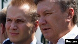 Украинанын мурдагы президенти Виктор Янукович уулу Александр менен.