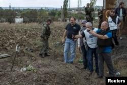Співробітники ОБСЄ фотографують могилу в Нижній Кринці