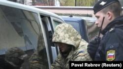Захваченный украинский военнослужащий выходит из микроавтобуса возле здания суда в Симферополе