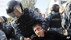 Riot police detain a demonstrator during a protest against the pilgrimage of Hassidic Jews in the town of Uman.