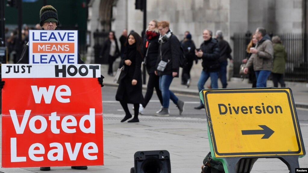 """Демонстрант с плакатами """"Мы голосовали за выход"""", """"Уйти значит уйти"""" перед зданием британского парламента в Лондоне. Справа от него знак """"Обход"""""""