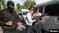 Полиция наразылық шарасына келгендердің бірін ұстап әкетіп барады. Алматы, 1 мамыр 2019 жыл.
