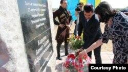 Люди возлагают цветы у памятной стелы Ахмаду Кадырову. Поселок Малая Сарань Карагандинской области. 23 августа 2012 года.