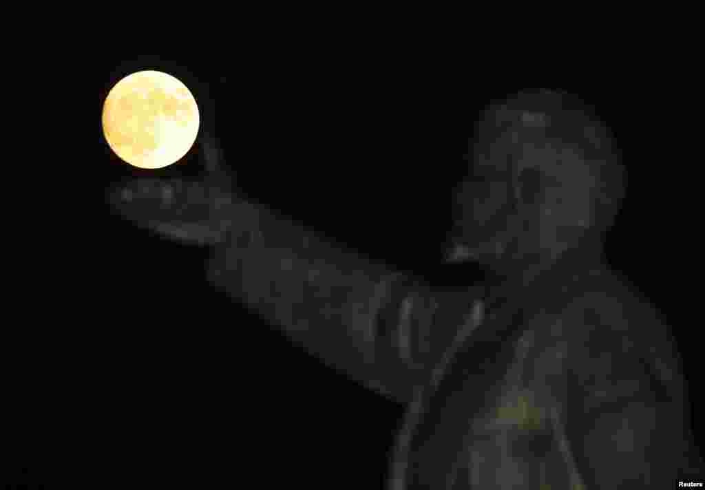 A so-called supermoon rises behind a statue of Soviet state founder Vladimir Lenin in Baikonur, Kazakhstan (Reuters/Shamil Zhumatov).