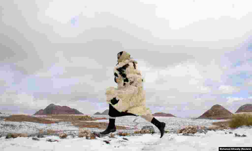 A woman runs through snow during a cold spell in the desert near Tabuk, Saudi Arabia, on February 1.