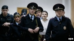 Ukrainian military pilot Nadia Savchenko (in white blouse) is escorted inside a Moscow court building for a hearing on April 17.