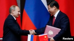 Russian President Vladimir Putin (left) and Chinese counterpart Xi Jinping shake hands after signing an agreement during a bilateral meeting in Shanghai on May 20.