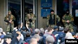 Пророссийские вооруженные люди охраняют вход в государственное учреждение в Славянске. 14 апреля 2014 года.