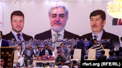 A campaign poster featuring Afghan CEO and presidential candidate Abdullah Abdullah (center) and his two running mates in Kabul on July 28.