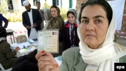 An Afghan woman shows her voter's pass for the August presidential election.