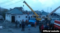 Authorities try to remove and sift through damage on November 3 after a roof collapsed at the Kara-Suu market in the Osh region of southern Kyrgyzstan.