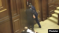 Armenia - Opposition deputy Aghvan Vartanian (L) helps an apparently drunk pro-government colleague, Arayik Grigorian, leave the parliament floor, Yerevan, 22May2014.