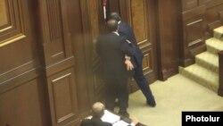 Armenia - Opposition deputy Aghvan Vartanian (L) helps an apparently drunk pro-government colleague, Arayik Grigorian, leave the parliament floor, Yerevan, 22May2014.