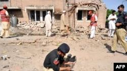 Тәліптер автоөкөлікте жарылыс жасаған жерді полиция өкілдері зерттеп жүр. Пешавар, Пәкістан, 20 мамыр 2011 жыл.