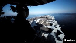 A U.S sailor keeps watch from the captain's bridge in the Strait of Hormuz.