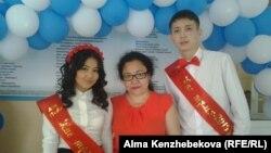 Заместитель директора по воспитательной работе школы-гимназии № 139 города Алматы Жанар Жусупова (в центре) с выпускниками школы. Алматы, 25 мая 2015 года.
