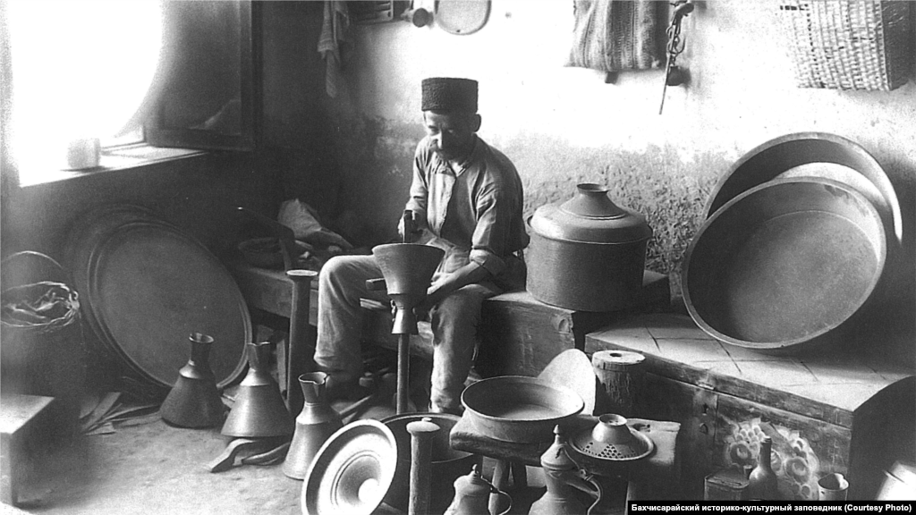 A coppersmith works in his shop in Bakhchysaray. Nonferrous metals were handled by coppersmiths. Household utensils were made of tin plated with copper, ritual vessels and chandeliers for mosques were made of brass. Coffee grinders were assembled from brass and iron parts.