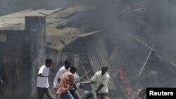 Жители Могадишо выносят пострадавшего с места взрыва, 4 октября 2011 г.