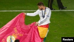 Portugal - Real Madrid's Sergio Ramos performs a bull fight as he celebrates after defeating Atletico Madrid in their Champions League final soccer match at the Luz Stadium in Lisbon May 24, 2014.