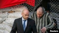 Сотрудник специальной миссии ОБСЕ в Украине покидает мэрию вместе с освобожденным наблюдателем, гражданином Швеции. Славянск, 27 апреля 2014 года.